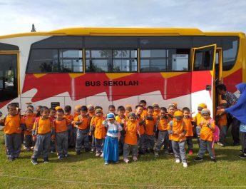 Anak-anak sedang foto bersama di samping bis yang mereka tumpangi